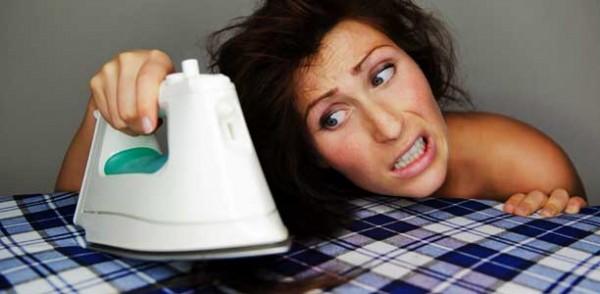 Mulher alisando o cabelo com o ferro de passar roupa
