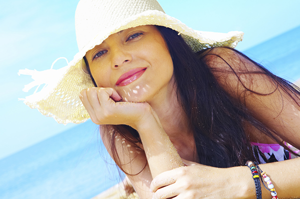 Mulher usando chapéu na praia