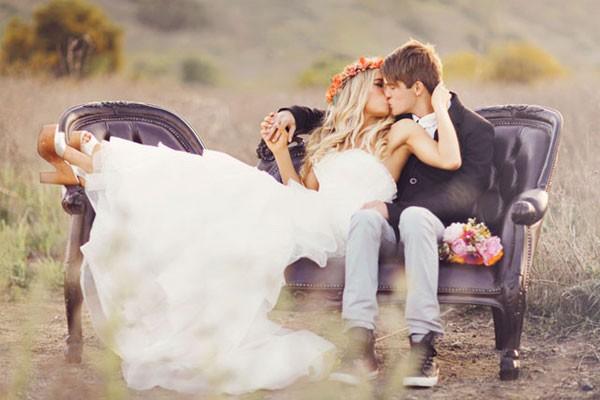 Foto do noivo beijando a noiva que está usando uma tiara de flores