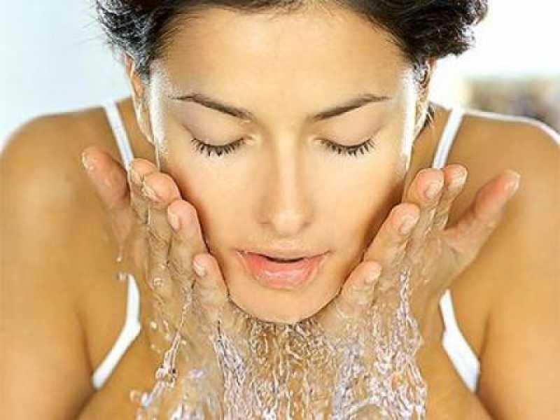 Mulher lavando o rosto para remover a maquiagem