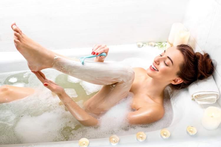mulher fazendo depilação com lâmina dentro da banheira
