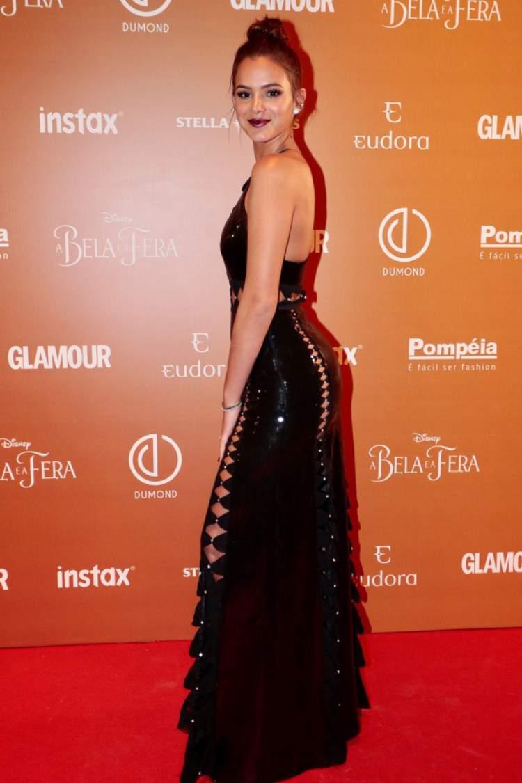 Bruna Marquezine usando vestido preto com recortes + batom roxo