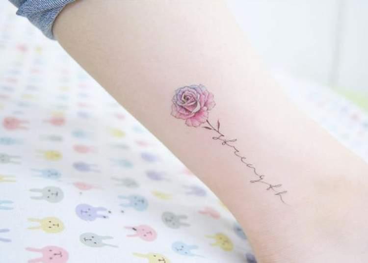 Tatuagem delicada om o desenho de flor