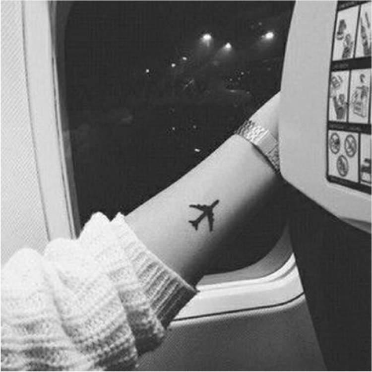 Tatuagem delicada de avião no braço