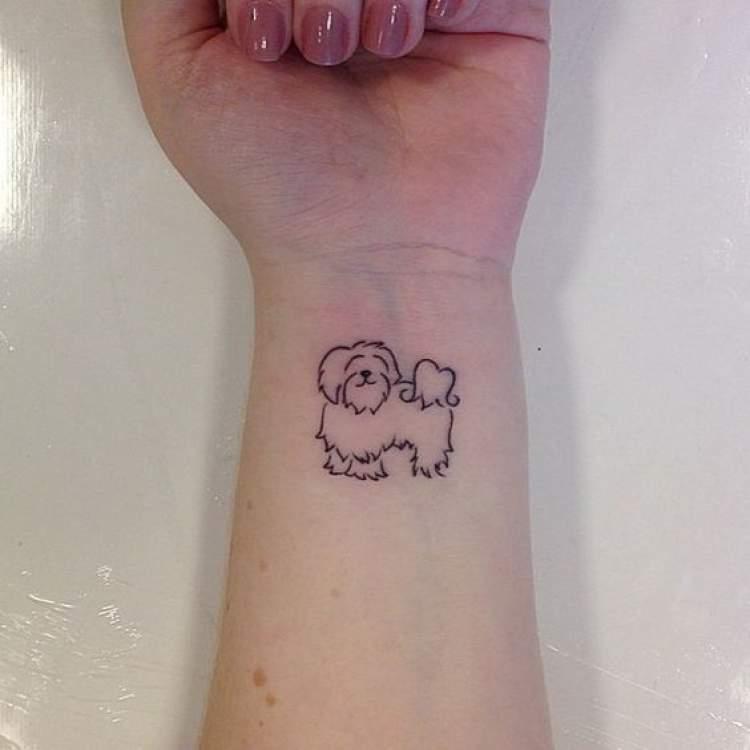 Tatuagem delicada de cachorro no punho