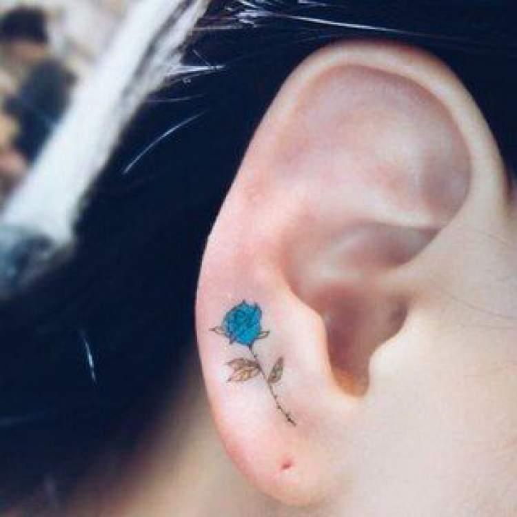 Tatuagem delicada de flor na orelha