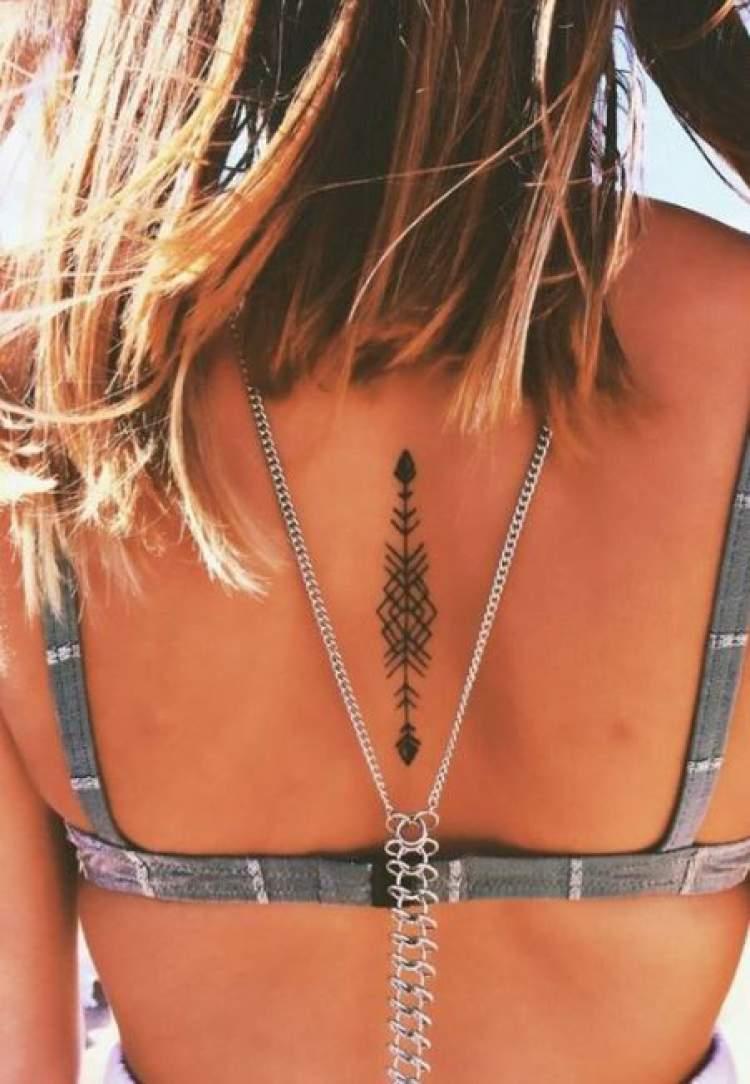 Tatuagem delicada nas costas com o desenho de uma flecha