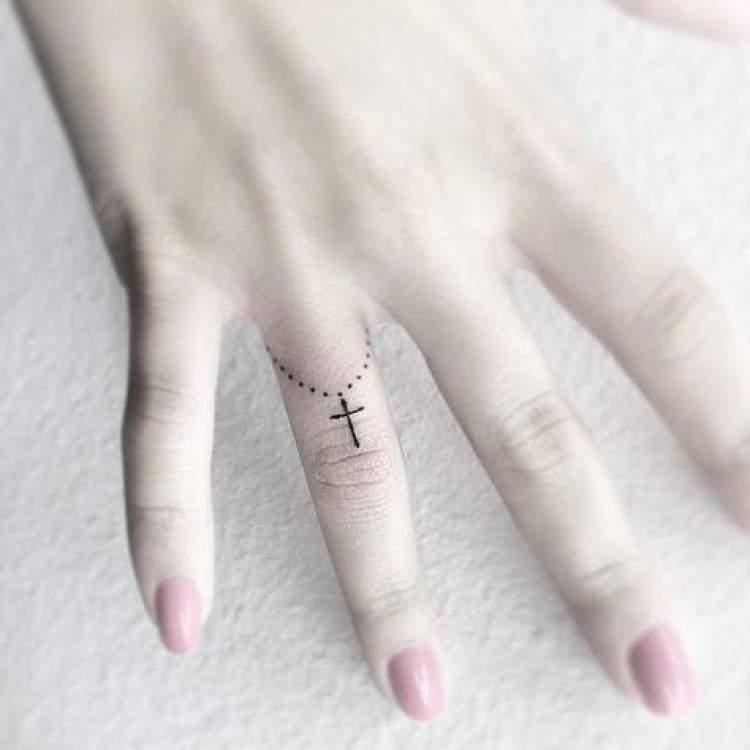 Tatuagem religiosa no dedo da mão