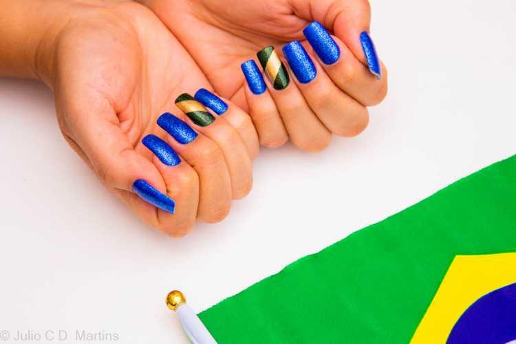 Bem clássicas, as unhas azuis ficam incríveis com uma filha única com as cores da bandeira brasileira em glitter.