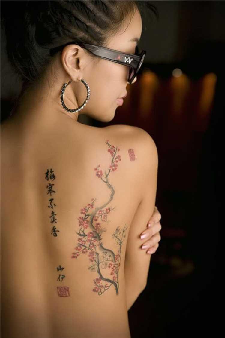 Mulher com parte das costas tatuada