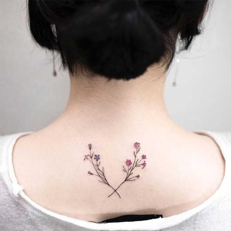 Tatuagem feminina com desenho de flores na parte superior central das costas próximo ao pescoço e nuca