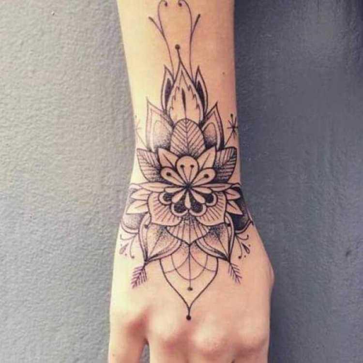 Tatuagem feminina na mão e no braço