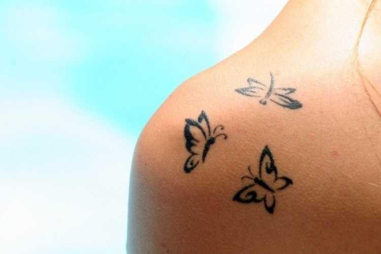 Tatuagem no ombro com o desenho de três borboletas