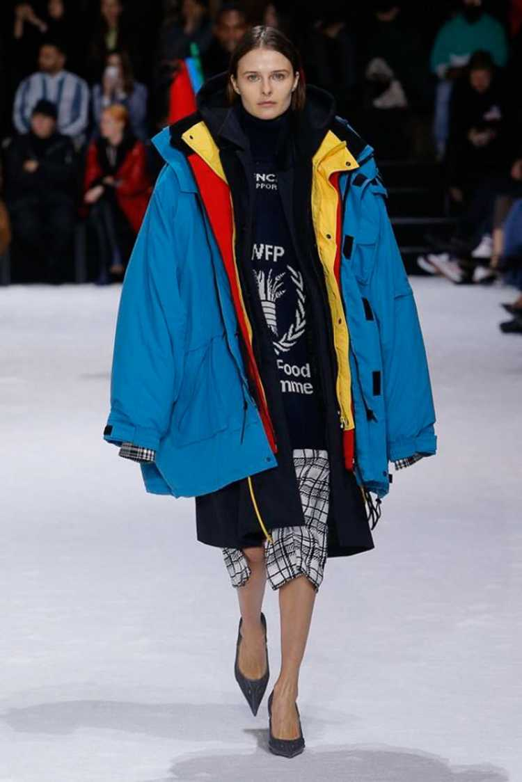 Modelo desfilando com peças sobrepostas para divulgar as tendências da moda inverno 2019.
