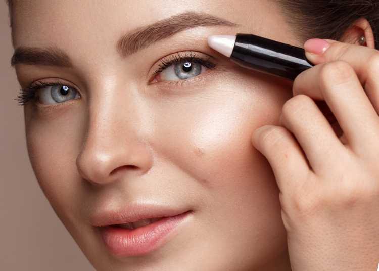 Maquiagem para sessão de fotos passando iluminador