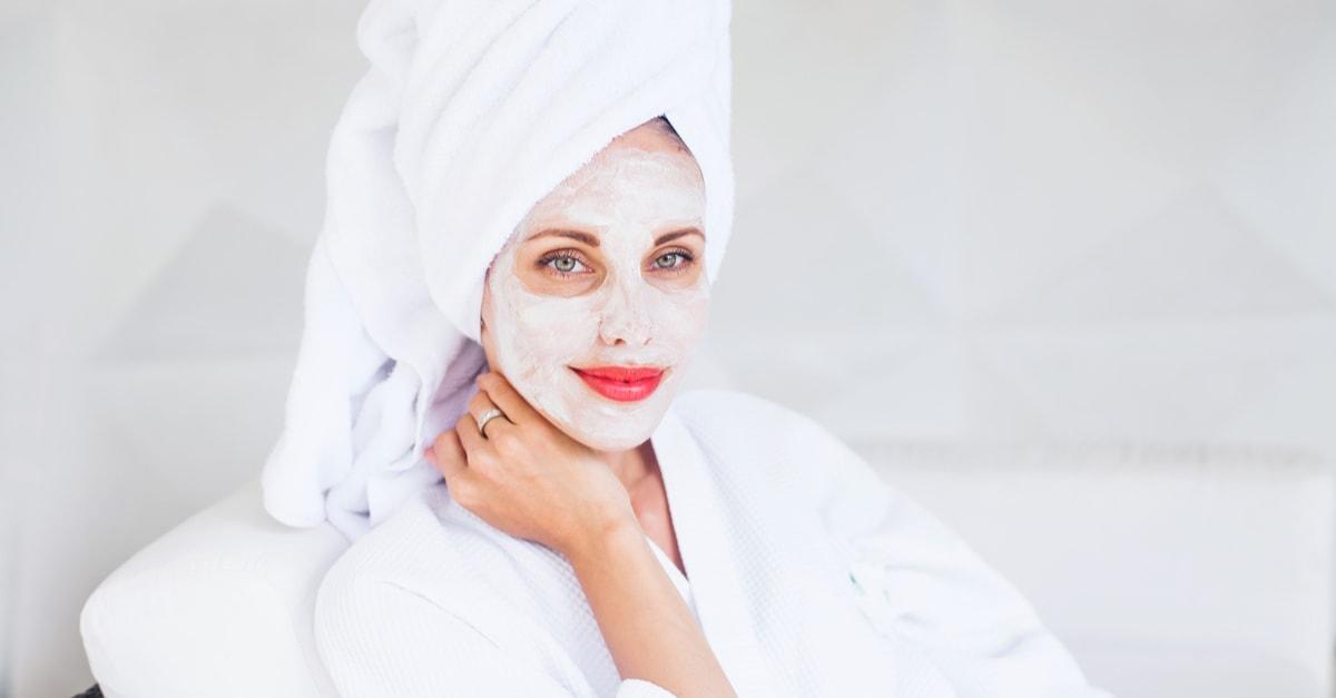 Mulher aplicando a máscara caseira e natural de açúcar e óleo de coco