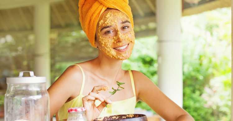 Mulher aplicando máscara caseira e natural de mel e mamão no rosto