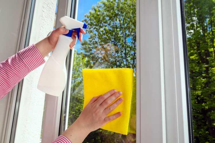 Limpando o vidro com toalha amarela e borrifador branco