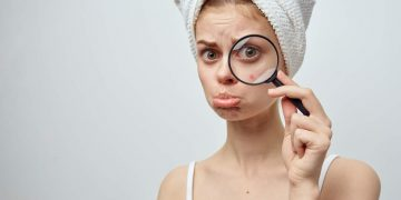 Mulher com lupa olhando espinha