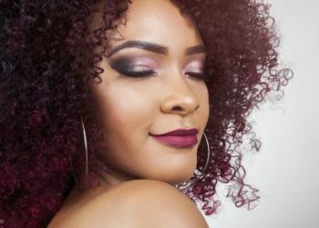 Mulher com cabelo cacheado colorido e corte médio